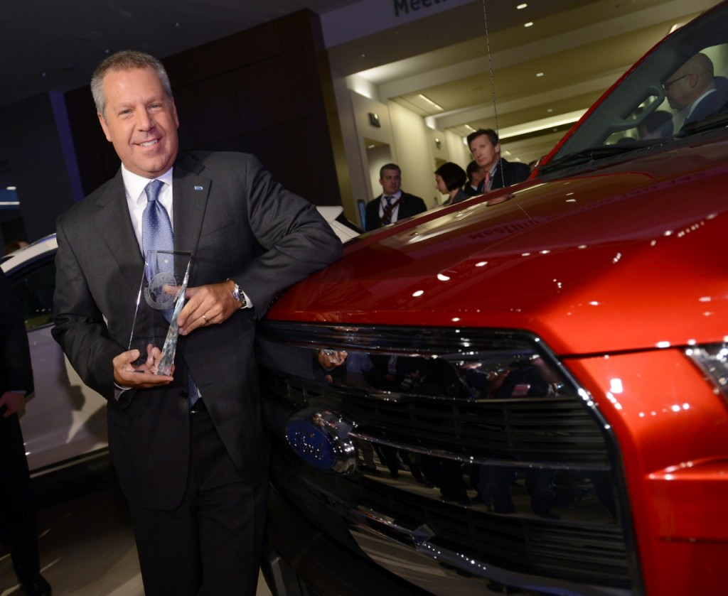 Joe Hinrichs, Ford president of The Americas, holds the TOTY trophy while leaning on the 2015 F-150