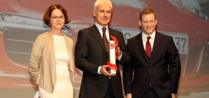 Porsche CEO Matthias Müller (center), accepting an award from Deputy Editor Birgit Priemer (left), and Editor-In-Chief Jens Katemann